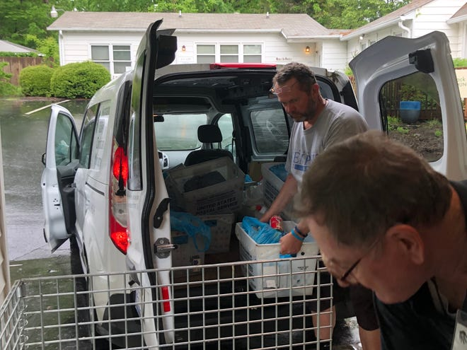 Swannanoa Valley Christian Ministry volunteers Jeff Erson and John Hash unload food bags collected by the Black Mountain and Swannanoa Post Office on May 11.