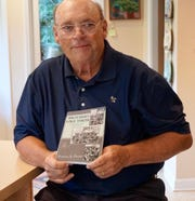 """David Rozzell holds a copy of """"Brothers Like These,"""" a collection of writing from a Vietnam veterans creative writing group at the Charles George VA Medical Center in Asheville."""