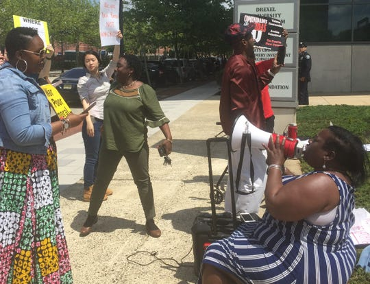 Vida Neil-Rosiji of Camden leads protesters in a chant outside meeting of elected and business leaders Thursday.