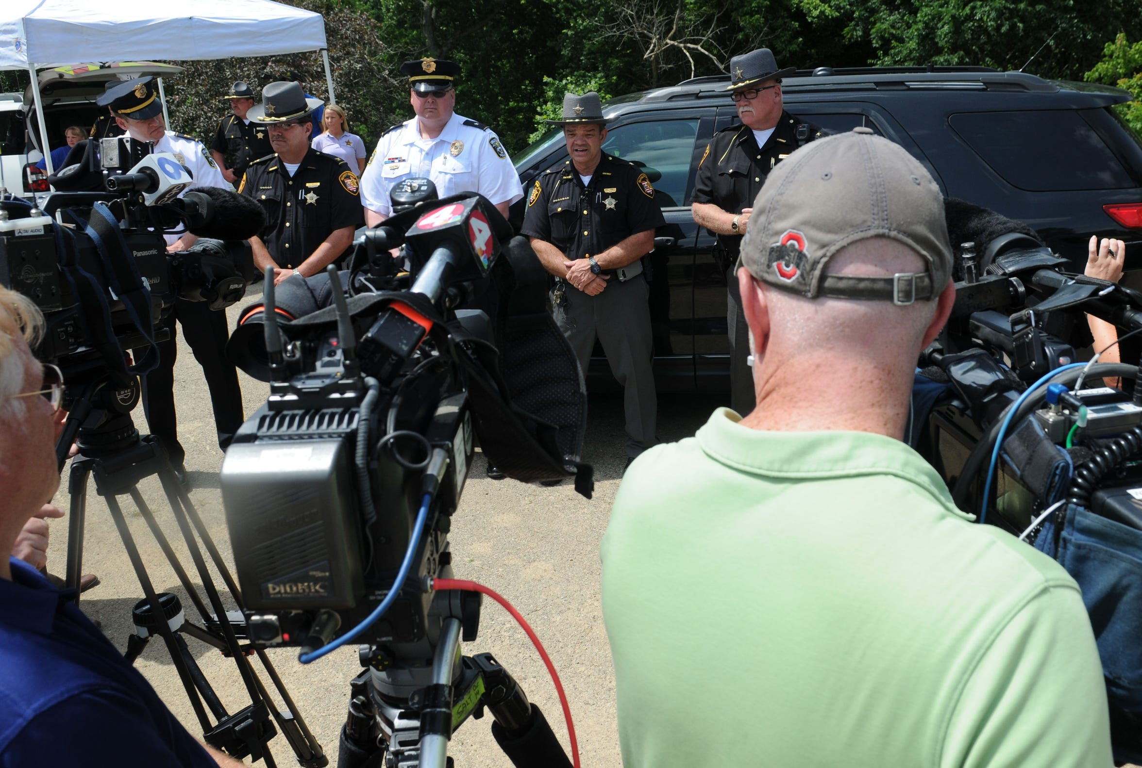 Local officials gather for a news conference after Tiffany Sayre's body was found off of Cave Road in June 2015.