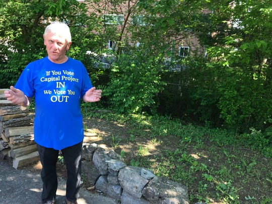 Glenn Hughes stands in front of where a massive development will be built by his house. He opposes the development.