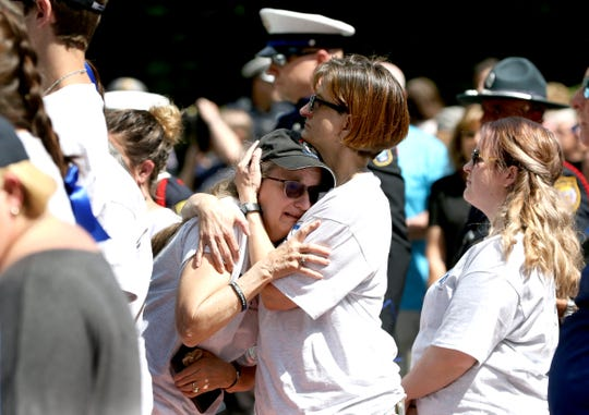 Ann Woods, mother of Colerain Township Police Officer Dale Woods, who was fatally struck at the scene of a traffic accident in January, is comforted during the annual police memorial ceremony at Fountain Square Friday, May 17, 2019.