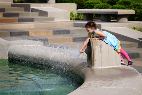 Anna Sellers, 5, of Finnerytown, dips her fingers into the water after the fountain was turned back on outside of the Cincinnati Museum Center at Union Terminal. The water had been turned off for three summers during renovations at the Museum Center.