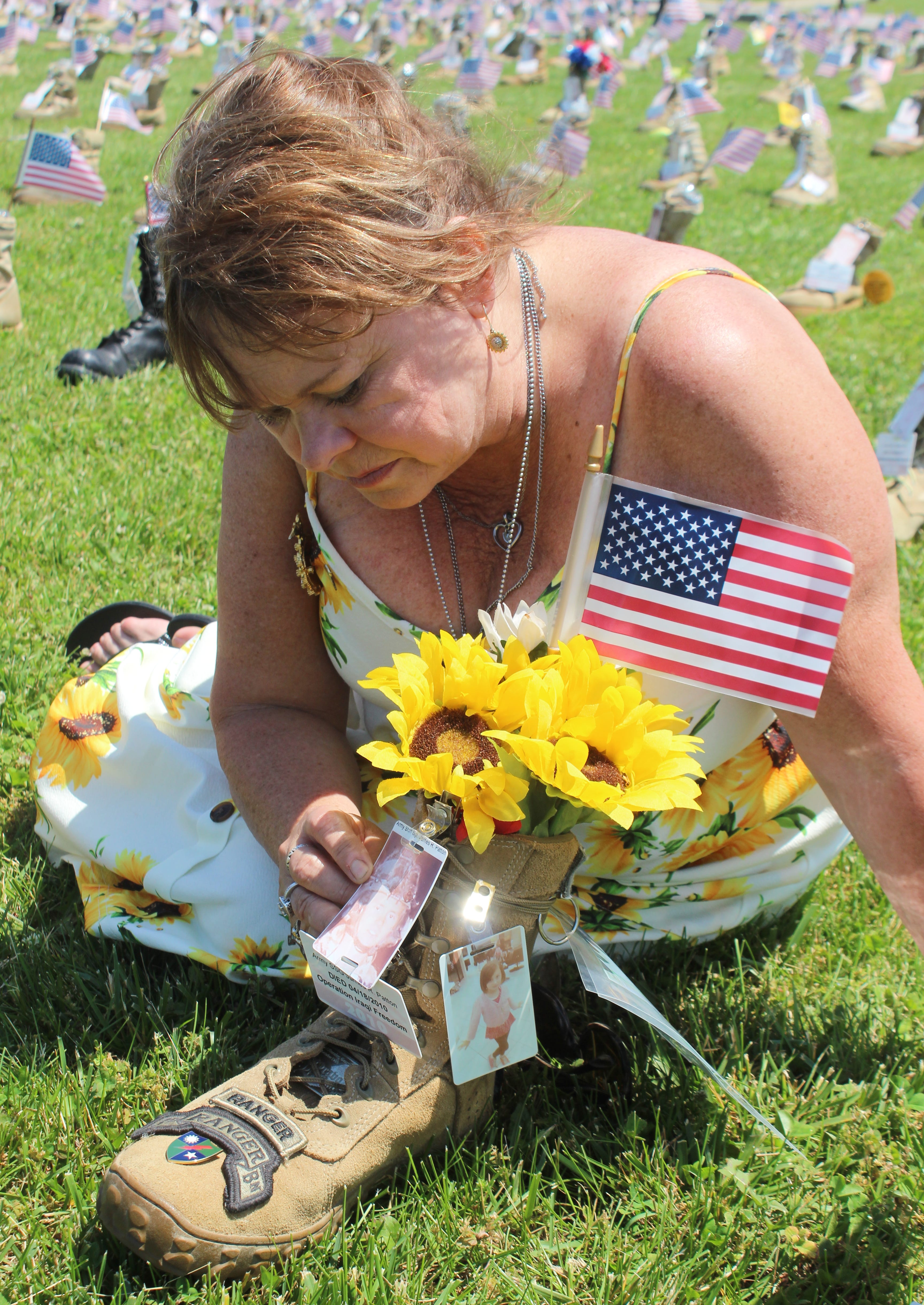 Sheila Patton sits beside the boot made in honor of her son, Staff Sergeant James R. Patton, who was killed in action in Iraq, which now sits as one of the 7,600 boots on display at Fort Campbell as part of the Boots on the Ground display honoring fallen service members on May 17, 2019.