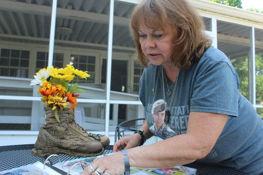 Sheila Patton examines a scrapbook filled with photos of the first boot display at Fort Campbell in honor of fallen service members, as her own son's boots sit in the background, on May 16, 2019.