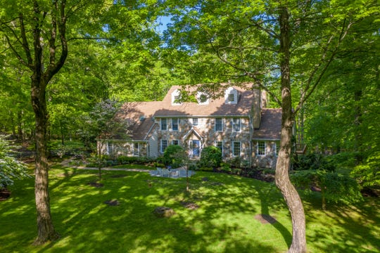 A stone front Colonial is for sale for $649,900 on nearly seven verdant acres in Clinton Township.