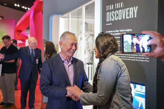 Actor George Takei,  who played  the helmsman Hikaru Sulu of the USS Enterprise in the television series Star Trek, shakes hands with Solan Darwish, 40, of Dearborn, as he tours the Start Trek: Exploring New Worlds exhibit at the Henry Ford museum in Dearborn, Mich. on Friday, May 17, 2019. Darwish says she is a big fan of Takei because of his political views and Twitter presence.