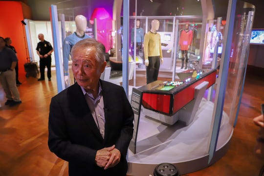 Actor George Takei stands in front of the original set where he played Hikaru Sulu, the helmsman of the USS Enterprise in the television series Star Trek, as he tours the Start Trek: Exploring New Worlds exhibit at the Henry Ford museum in Dearborn, Mich. on Friday, May 17, 2019.