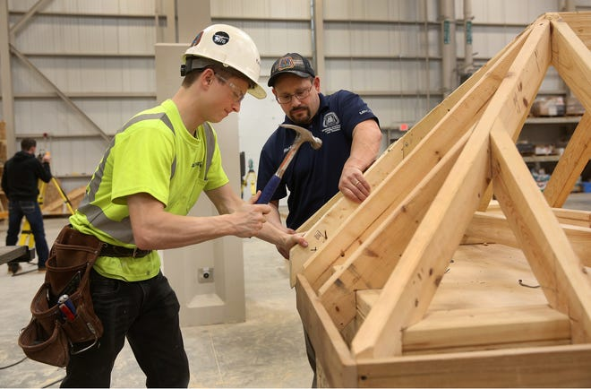 Instructor Mark Silvestri, right, assists carpenter's apprentice Jacob Atkins, 21. The Kalamazoo Promise is partnering with the Michigan Regional Council of Carpenters and Millwrights to provide scholarship funds for the apprenticeship program.