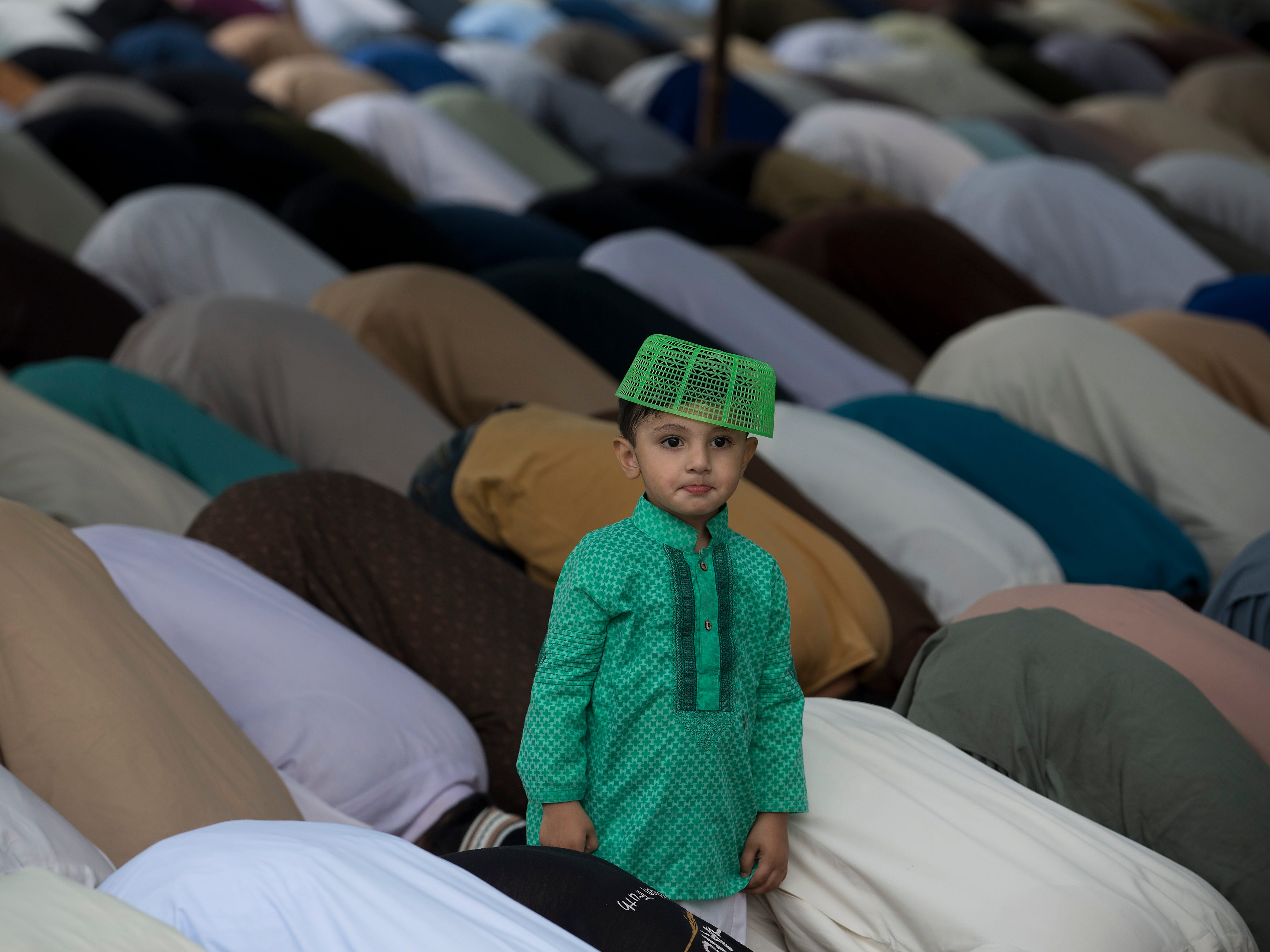 A Pakistani boy stands amid a crowd of Muslims offering prayers at a mosque on the second Friday of Ramadan in Rawalpindi, Pakistan, May 17, 2019. Muslims throughout the world are marking Ramadan, the holiest month in the Islamic calendar, in which devotees refrain from eating, drinking, smoking and sex from sunrise to sunset.