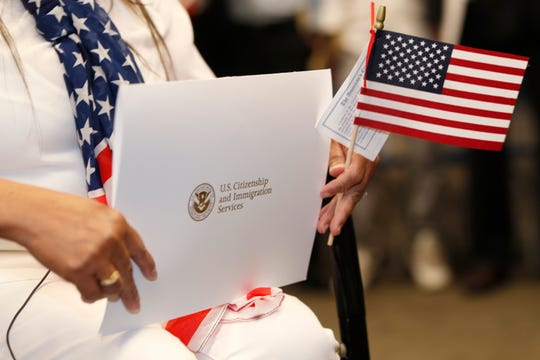 Vivian Ragan holds the envelope containing her United States citizenship papers and an American flag at a naturalization ceremony, Thursday, May 16, 2019, in Centennial, Colo.