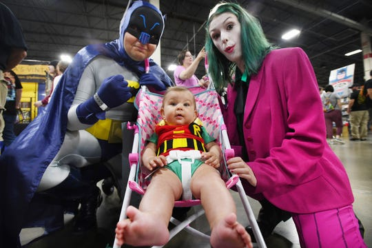 Tim Parrelly with wife Ehlana Parrelly and daughter Ellie Parrelly, 5 months, look the part in classic Batman, Robin and the Joker outfits at Motor City Comic Con.