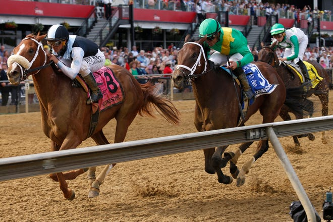 Point of Honor, left, with Javier Castellano aboard wins the Black-Eyed Susan race at Pimlico Race Course. Ulele (3) with Joel Rosario atop finishes second with Cookie Dough with Irad Ortiz Jr. onboard places third.