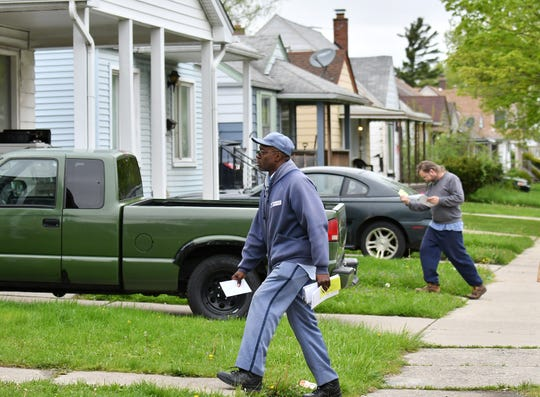 U.S. Postal Service employee Michael Harris delivers mail in the Warrendale neighborhood in Detroit on May 13. Harris has had a route in this area for 18 years.