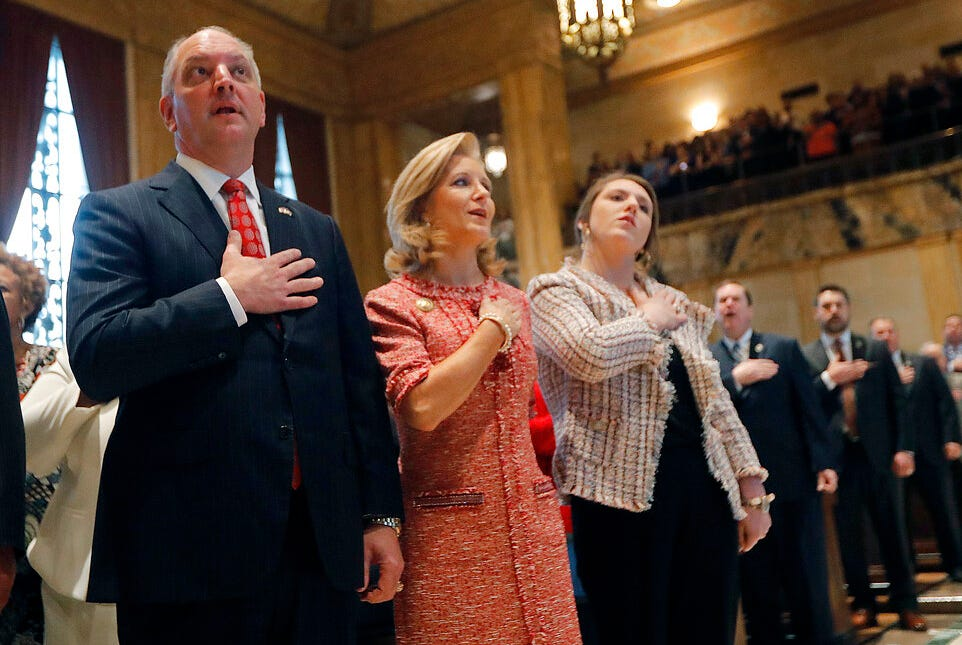 In this  Monday, April 8, 2019 file photo, Louisiana Gov. John Bel Edwards pledges allegiance with his wife, Donna Edwards, and their daughter Sarah Ellen Edwards, right, during the opening of the annual state legislative session in Baton Rouge, La.