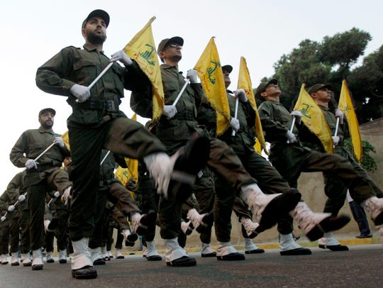 In this Nov. 12, 2010 file photo, Hezbollah fighters parade during the inauguration of a new cemetery for their fighters who died in fighting against Israel, in a southern suburb of Beirut, Lebanon.