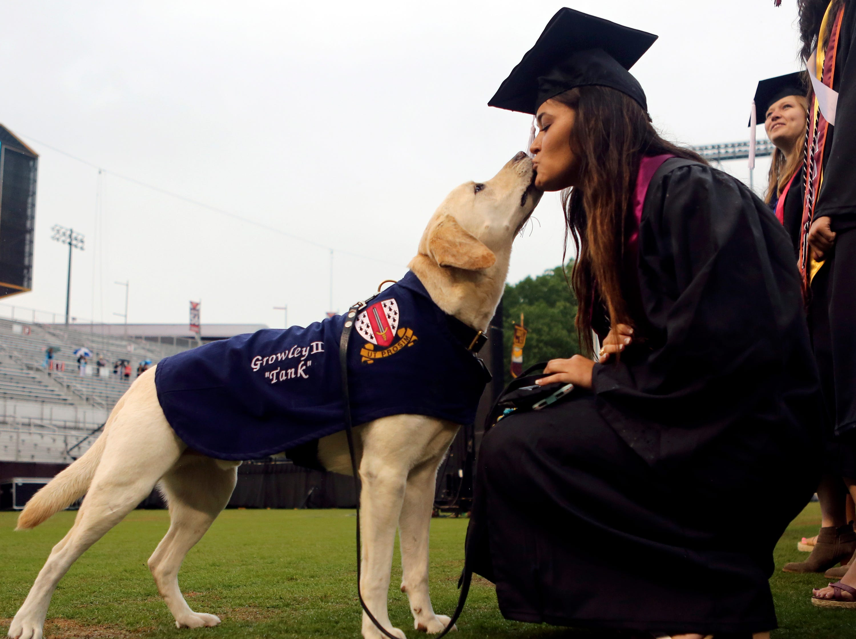 Graduate Eleanor Franc gets a kiss from Virginia Tech Corps of Cadets ambassador Growley II at the start of graduation in Blacksburg, Va. Friday May 17, 2019. Franc is one of a team of handlers for Growley II who will stay on campus with the corps.