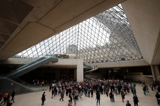 Le Louvre museum employees and tourist gather under the giant glass pyramid by late architect I.M. Pei, Friday, May 17, 2019 in Paris.