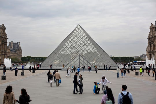 Tourists walk around the pyramide of the Louvre museum, in Paris, Friday, May 17, 2019.
