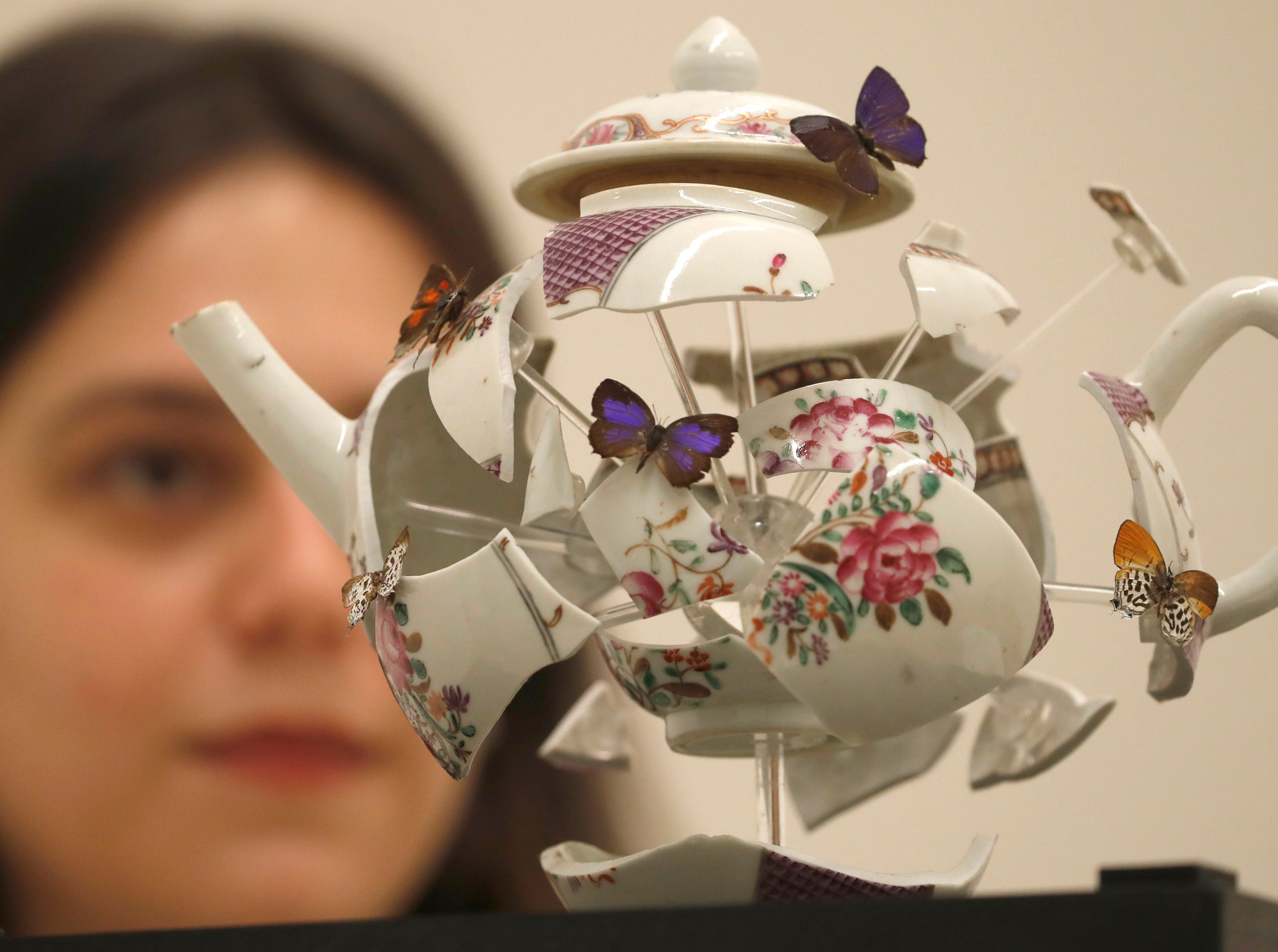 """A Christies employee checks an artwork by Bouke De Vries entitled """"Deconstructed Teapot with Butterflies"""" 2017, at Christie's auction house in London, Friday, May 17, 2019. The teapot is expected to sell for $5,100-$7,600) at auction on May 22."""