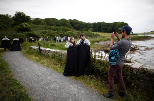 "In this June 13, 2014, file photo ""Game of Thrones"" fans stop for a picture on their way to Audleys field and castle, castleward, Strangford, Northern Ireland."