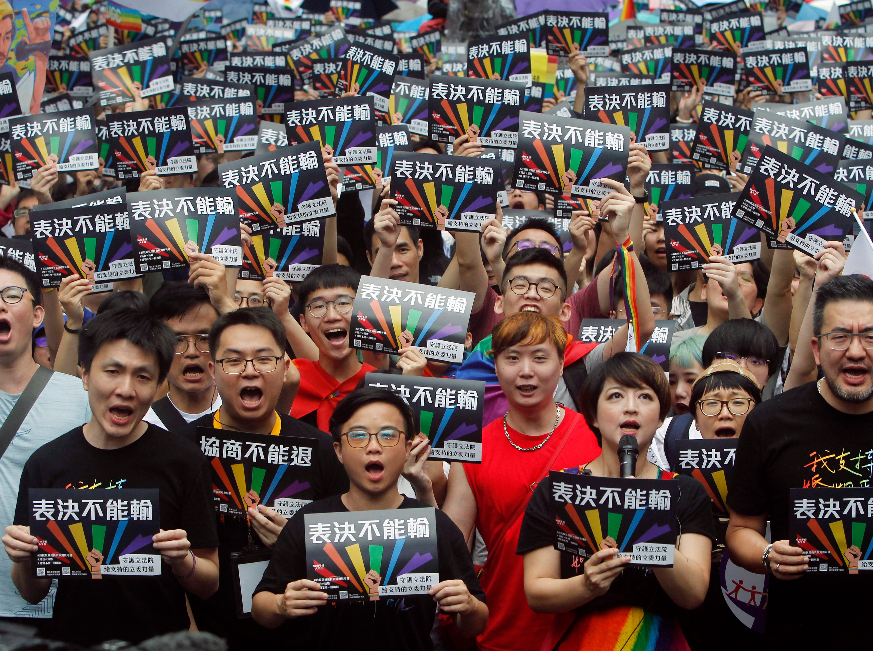 Same-sex marriage supporters gather outside the Legislative Yuan in Taipei, Taiwan, Friday, May 17, 2019. Taiwan's Constitutional Court are scheduled to decide Friday on legalizing same-sex marriage, marking a potential first in Asia. The signs read  ''Vote Can't Be Defeated.''