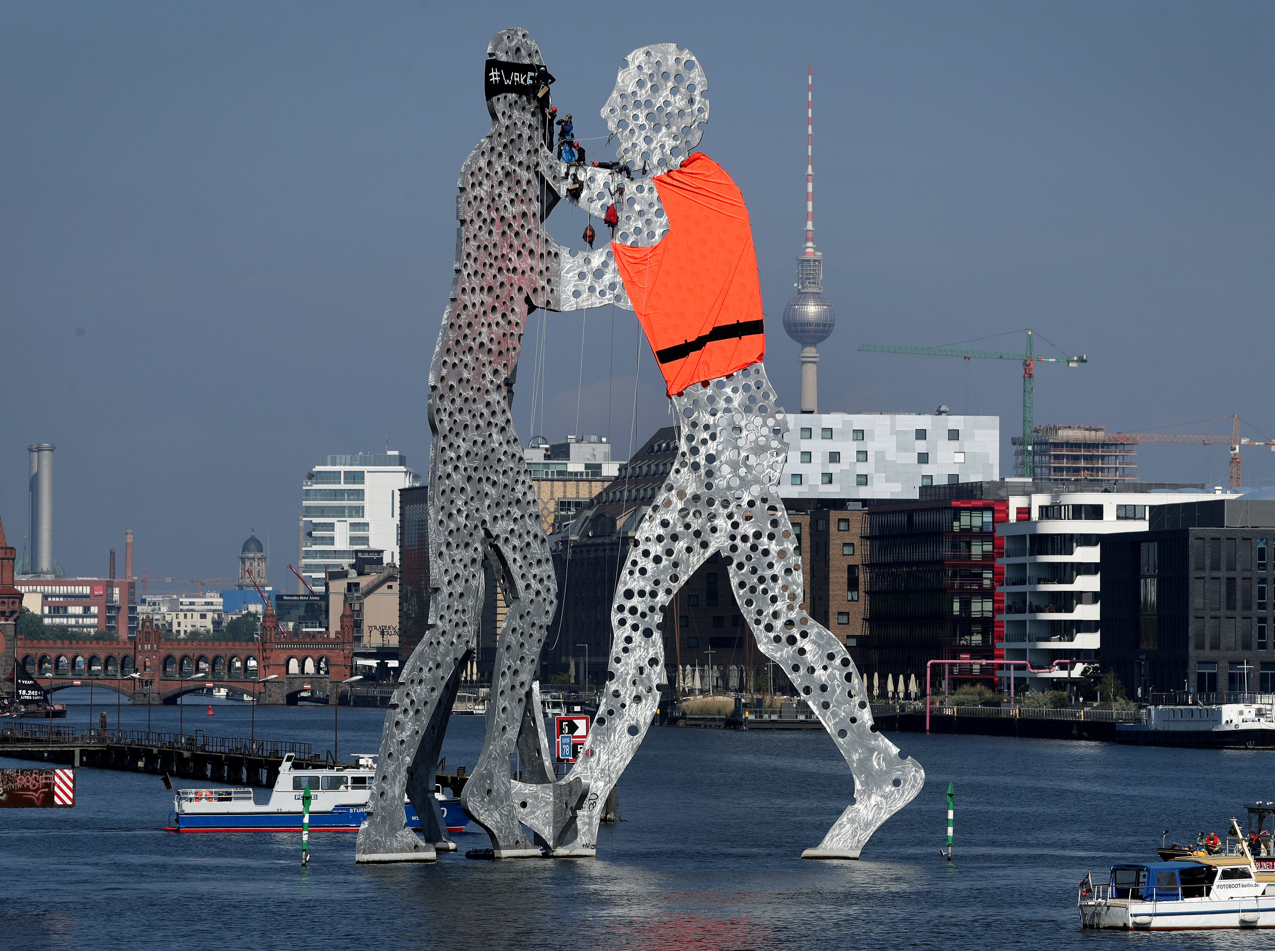 """Activists add a life vest to the capital's iconic """"Molecule Man"""" statue in Berlin, Germany, Friday, May 17, 2019. Protesters climbed the 100-foot tall artwork, which towers out of the Spree river in downtown Berlin, to adorn the statue with an orange vest and to raise the awareness to the perilous plight of migrants attempting to cross the Mediterranean into Europe."""