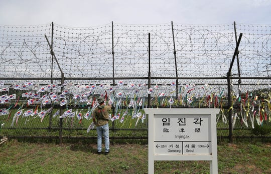 A man adjusts national flags on wire fences near a directional sign showing the distance to North Korea's Kaesong city and South Korea's capital Seoul at the Imjingak Pavilion in Paju, South Korea.