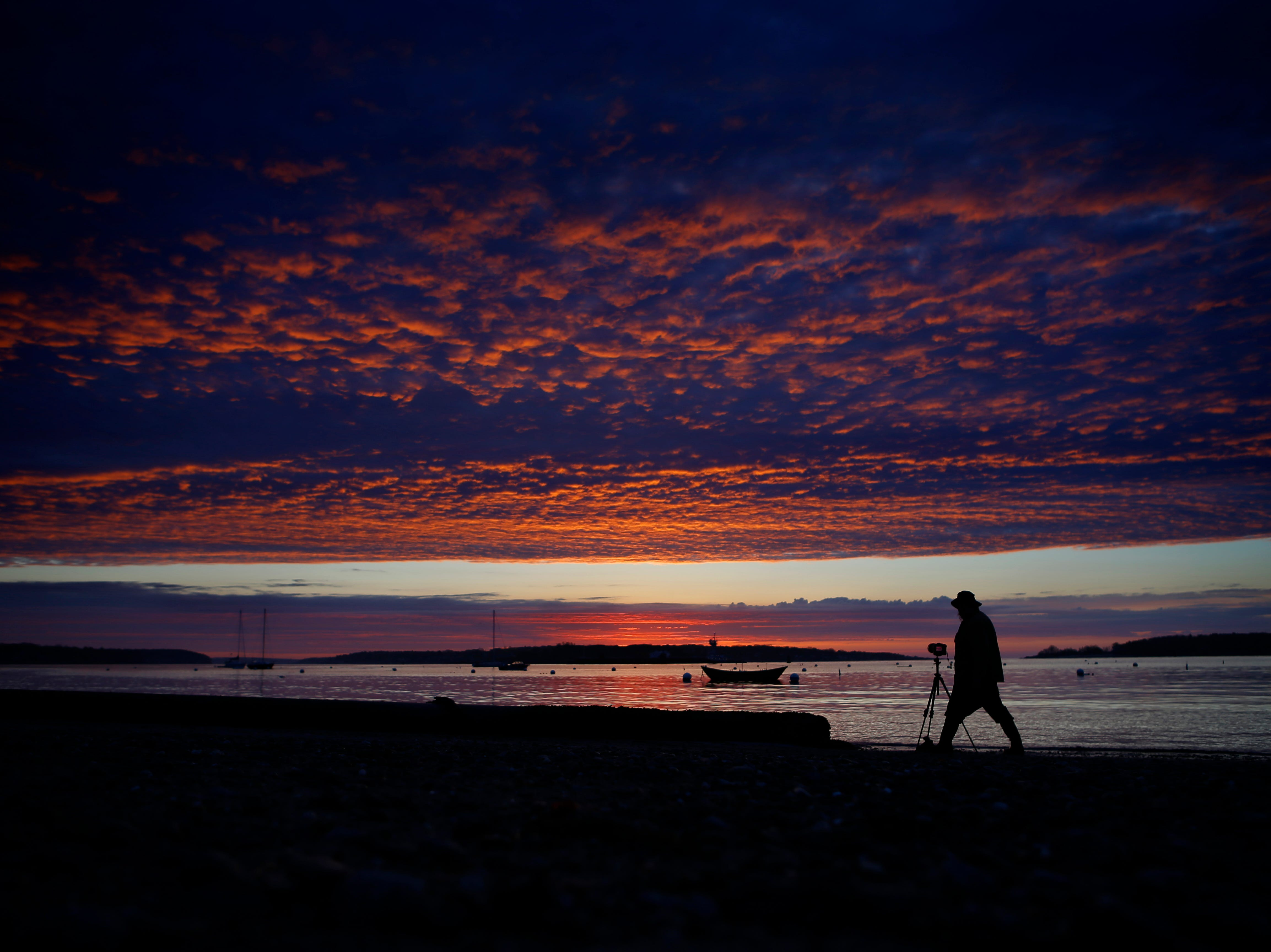 A mackerel sky is colored by the first rays of sunlight as Chuck Johns photographs a dory moored off Willard Beach, Friday, May 17, 2019, in South Portland, Maine. The color was fleeting as rain clouds moved in shortly after sunrise. New England, like much of the country, continues to experience wetter-than-usual weather.