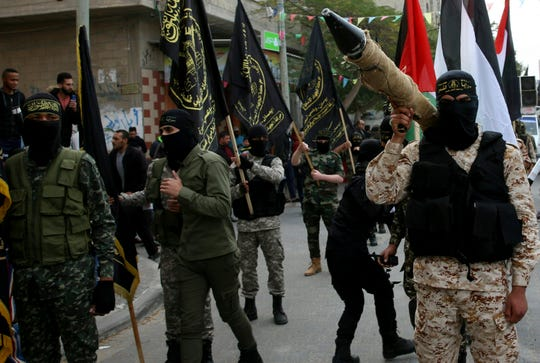 In this Dec. 22, 2017 file photo, masked members of the Palestinian Al-Quds Brigades, the military wing of the Islamic Jihad group, march with their rifles during a protest against U.S. President Donald Trump's decision to recognize Jerusalem as Israel's capital, in Nusseirat refugee camp, central Gaza Strip.