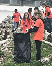 Students from Edison High School in Elmira Heights clean up litter and debris Friday from the banks of the Chemung River in downtown Elmira.