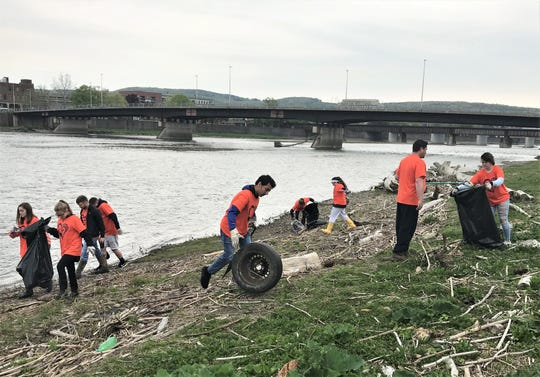 Students from Edison High School in Elmira Heights clean up litter and debris Friday morning from the banks of the Chemung River in Elmira.