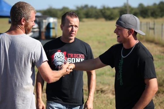 "Chris Libak (right) and Michael Wilke shake hands before racing on Discovery Channel's ""Dirty Mudder Truckers."""