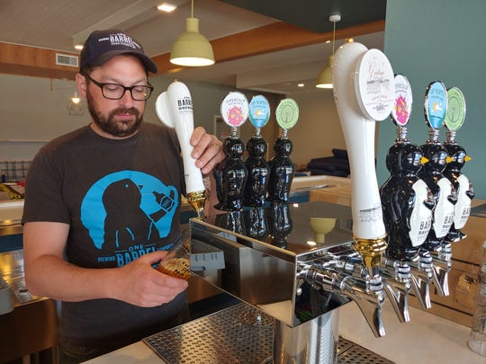 One Barrel Brewing Co. founder and president Peter Gentry pulls the tap handle to pour a beer in the craft brewery's new tap room opening May 23.