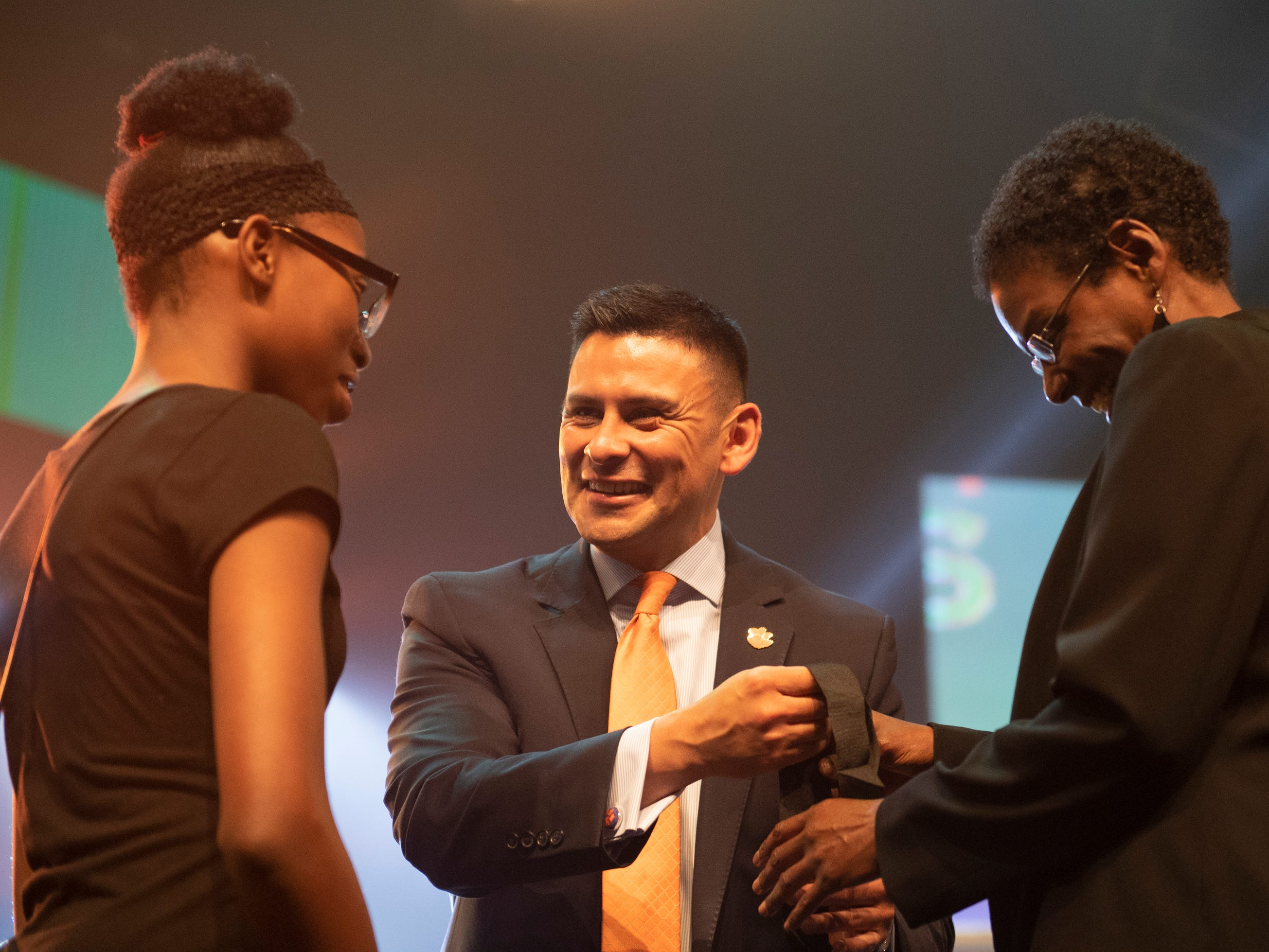 Julio Hernandez, chief of staff at the Division of Inclusion and Equity at Clemson University, presents Ya'Quiyah Thomas and her mentor, Cheryl Allen, with a medal for Thomas during the Coaches 4 Character ACE Awards held at Relentless Church Wednesday, May 15, 2019.