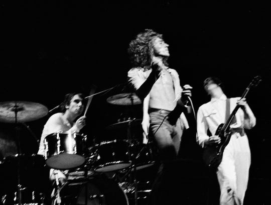 Pete Townshend, right, wears a white boiler suit during a 1970 performance with the Who (featuring Keith Moon, left, and Roger Daltrey).