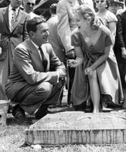 Actress Virginia Mayo and Tony Hulman after she signed her name on the concrete cast of her hand and footprints at the Indianapolis Motor Speedway in 1956.