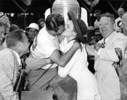Bill Holland, winner of the 1949 Indianapolis 500, plants a kiss on actress Linda Darnell in victory lane.