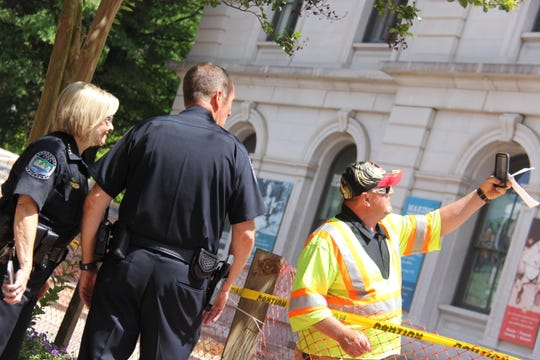 Johnny Fritts of McKinnnon Construction stops work on Market Street to take photos with two Knoxville Police Department officers May 16, 2019. The Market Street project involved removing eight trees to install new tree wells, as well as new sidewalks, curbs and street lights.