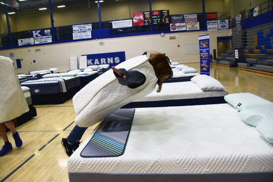 Mariam Layton, 16, takes a dive onto a mattress at the mattress sale fundraiser held at Karns High School on Saturday, May 11, 2019.
