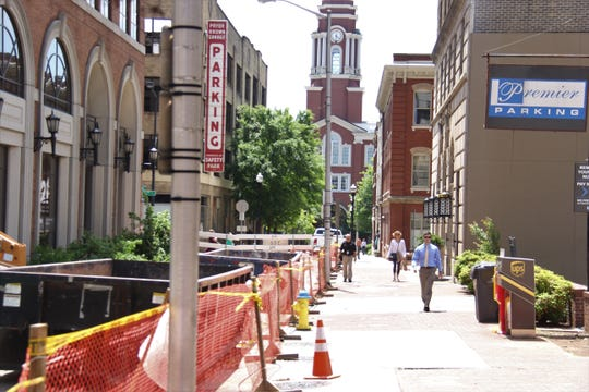 Pedestrians walk down the Market Street sidewalk as construction takes place May 16, 2019. One side of the sidewalk will be closed at a time until about mid-October.