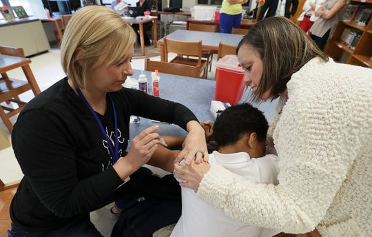 Amanda Burks, left, with Megan Habich, right, with JCPS, vaccinates a student at Waller-Williams Environmental School.