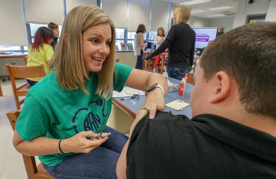 Blaire Adams, with JCPS, vaccinates a student at Waller-Williams Environmental School.