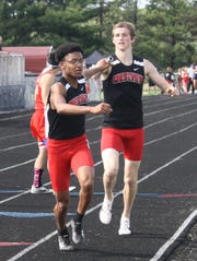 James Barber takes the baton for the anchor leg from Ross Kuhn as Crestview breezes to a Division III district title in the 4x800 relay.