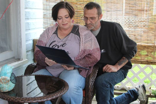 Cyndi Smith and her husband Ken look at an Associate's in Science degree that she recently earned at Marion Technical College. An accomplishment the 49-year-old thought would have been impossible for her just a few years ago.