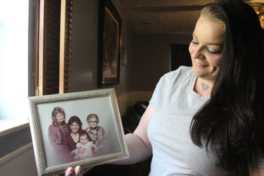 Adena Pennington holds up a picture of her mom, Julie Pennington, holding her as a baby. Julie was the 10th person to die of an accidental drug overdose in Marion County in 2018, according to autopsy reports from the Marion County Coroner's Office.