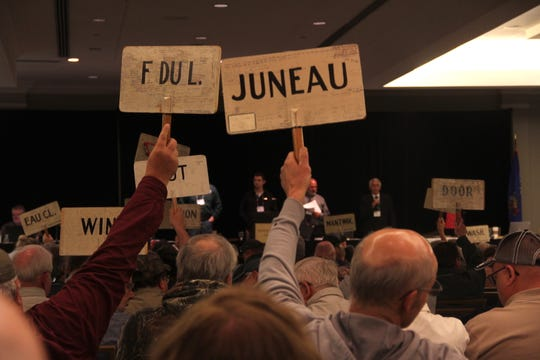 County delegations raise paddles to vote during a session of the 2019 Wisconsin Conservation Congress convention in Appleton.