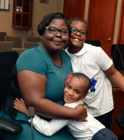 Latoya Onuchuku gets hugs from her grandchild, Zai'ema Johnson, 6, and her daughter, Za'mya Onuchuku, 9, before a reception for graduates in the first group of MATC Promise for Adults students.
