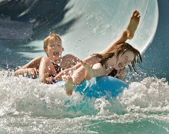 Children make a large splash at the end of a water tube while swimming in Greenfield Park Cool Waters pool in West Allis.