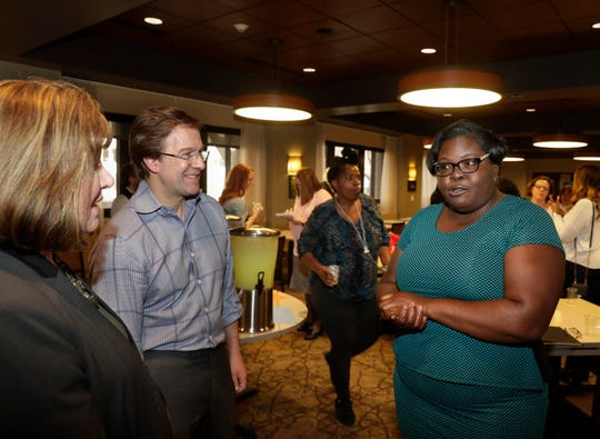 Latoya Onuchuku, 42, right describes the challenges she overcame to graduate in the first batch of MATC Promise of Adults students. She was chatting with Milwaukee County Executive Chris Abele and Milwaukee Area Technical College President Vicki Martin at a reception before graduation ceremonies.